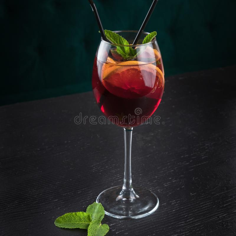 Cold sangria in a wine glass with mint. Cold sangria in a wine glass. Black wooden table in a restaurant royalty free stock images