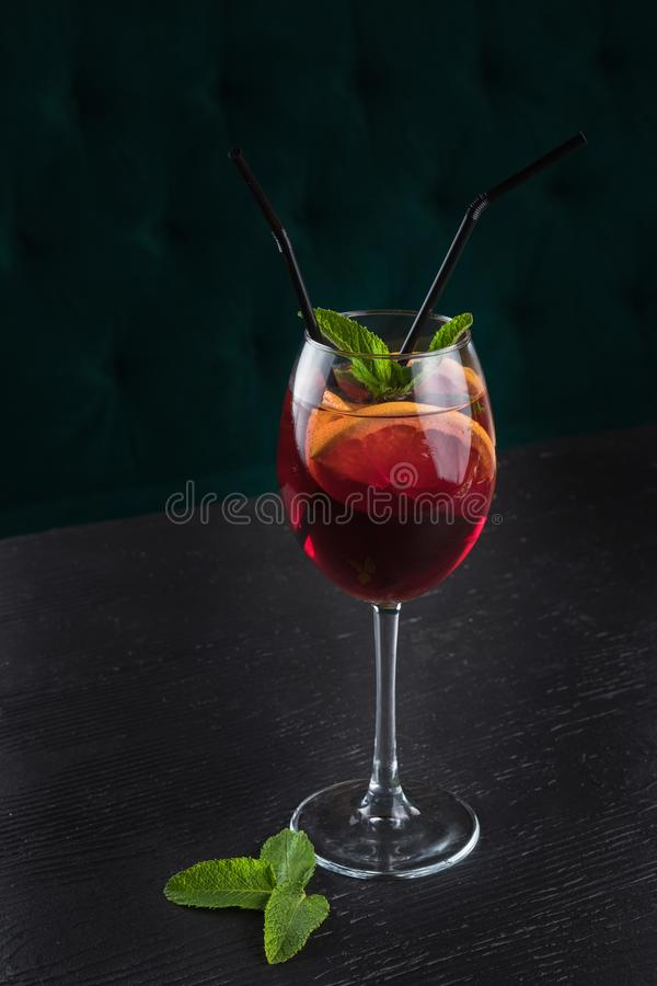 Cold sangria in a wine glass with mint. Cold sangria in a wine glass. Black wooden table in a restaurant royalty free stock photos