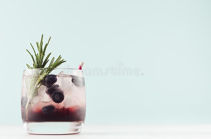 Cold shot in glass with blueberry, ice cubes, rosemary, straw in trendy modern bar interior in pastel mint color on white wood. Cold shot in glass with royalty free stock photos
