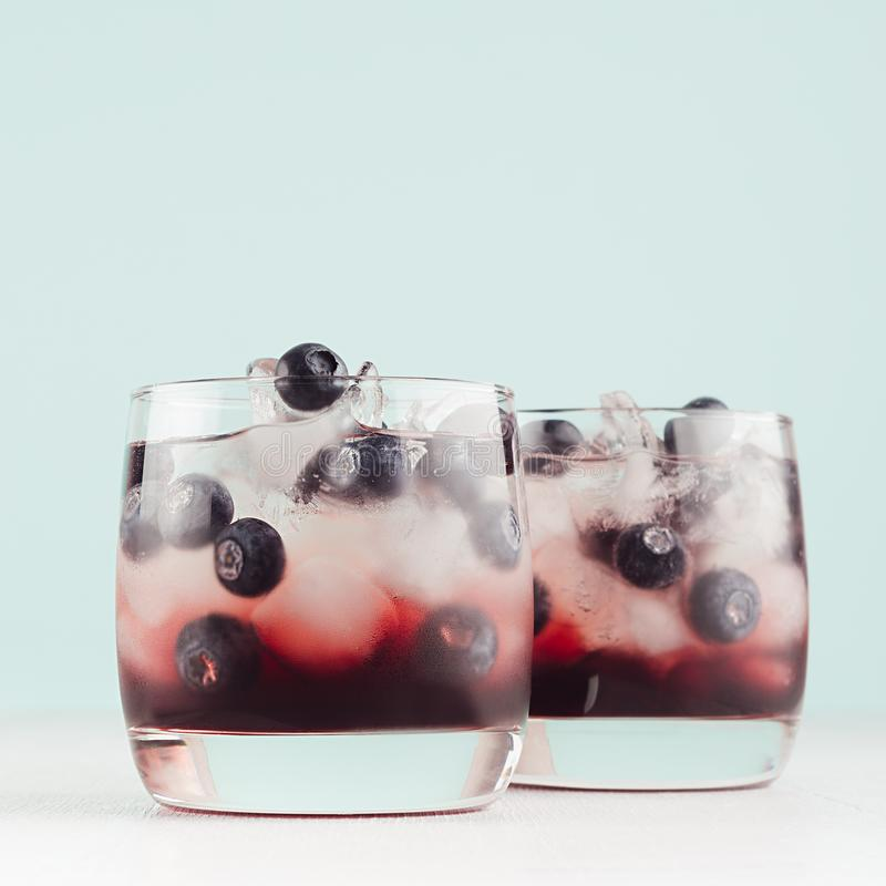 Cold shots in two glasses with blueberry, ice cubes in trendy modern bar interior in pastel mint color on white wood board, square.  stock photo