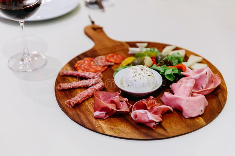 Cold smoked meat plate with prosciutto, salami, bacon, pork chops, cheese and olives on wooden plate with red wine . Cold smoked meat plate with prosciutto stock image