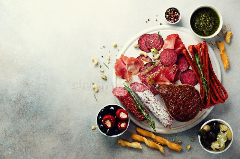 Cold smoked meat plate. Traditional italian antipasto, cutting board with salami, prosciutto, ham, pork chops, olives on royalty free stock photo
