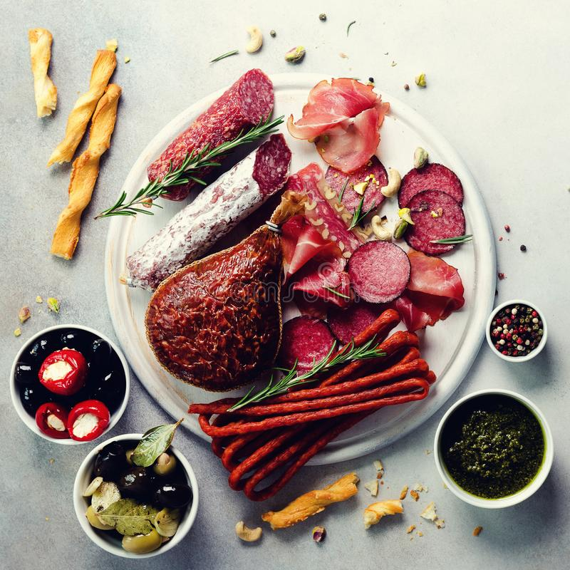Cold smoked meat plate. Traditional italian antipasto, cutting board with salami, prosciutto, ham, pork chops, olives on stock photos