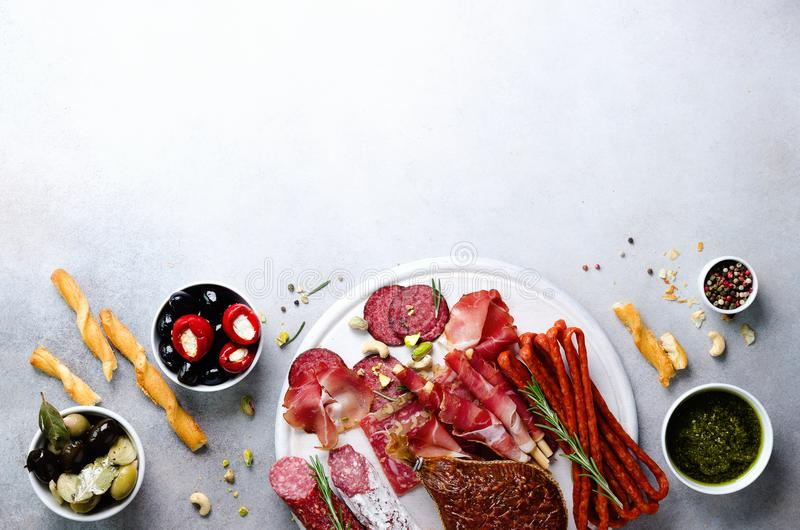 Cold smoked meat plate. Traditional italian antipasto, cutting board with salami, prosciutto, ham, pork chops, olives on. Grey background. Top view, copy space royalty free stock image