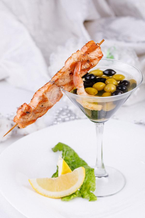 Cold snack from shrimps and fish shish kebab with original serving of olives in an elegant glass. Close-up stock photo