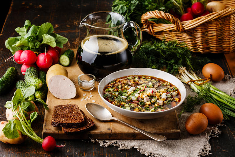 Cold Soup Okroshka. With sausage, vegetables and kvass serving size in bowl and raw ingredients on wooden table royalty free stock photo