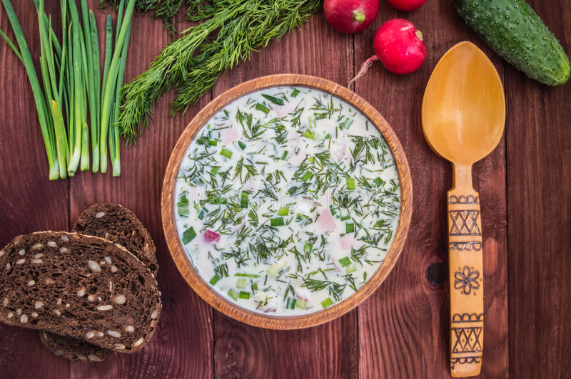 Cold soup okroshka. wooden background. Summer cold soup with radish, cucumber, and dill on wooden table. Okroshka royalty free stock photos
