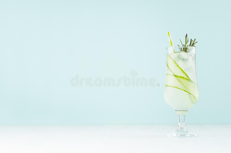 Cold sour muddy homemade cocktail with ice cubes, cucumber slice, rosemary, straw in soft light mint color bar interior. Cold sour muddy homemade cocktail with royalty free stock photography