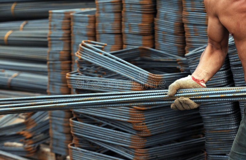 Cold steel. People carrying cold steel bars in the construction site royalty free stock photo