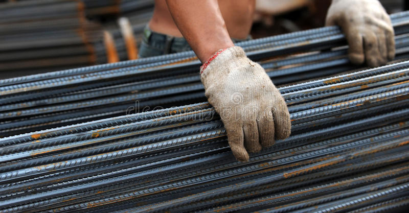 Cold steel. People carrying cold steel bars in the construction site royalty free stock image