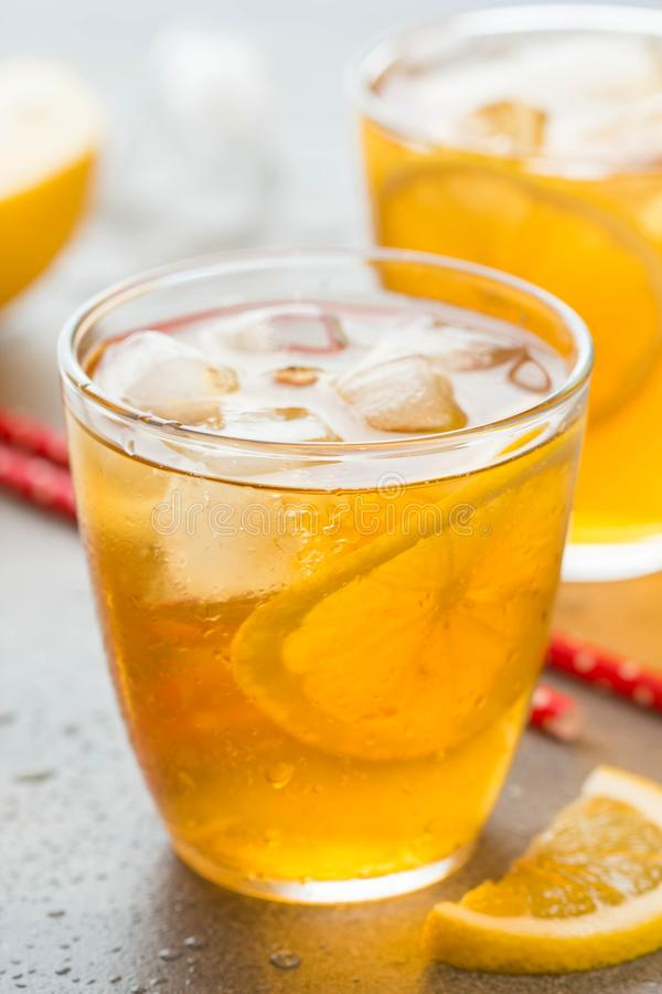 Cold tea with lemon and ice in a glass with drops, fresh sweet fruit drink, summer freshness, delicious lemonade royalty free stock images