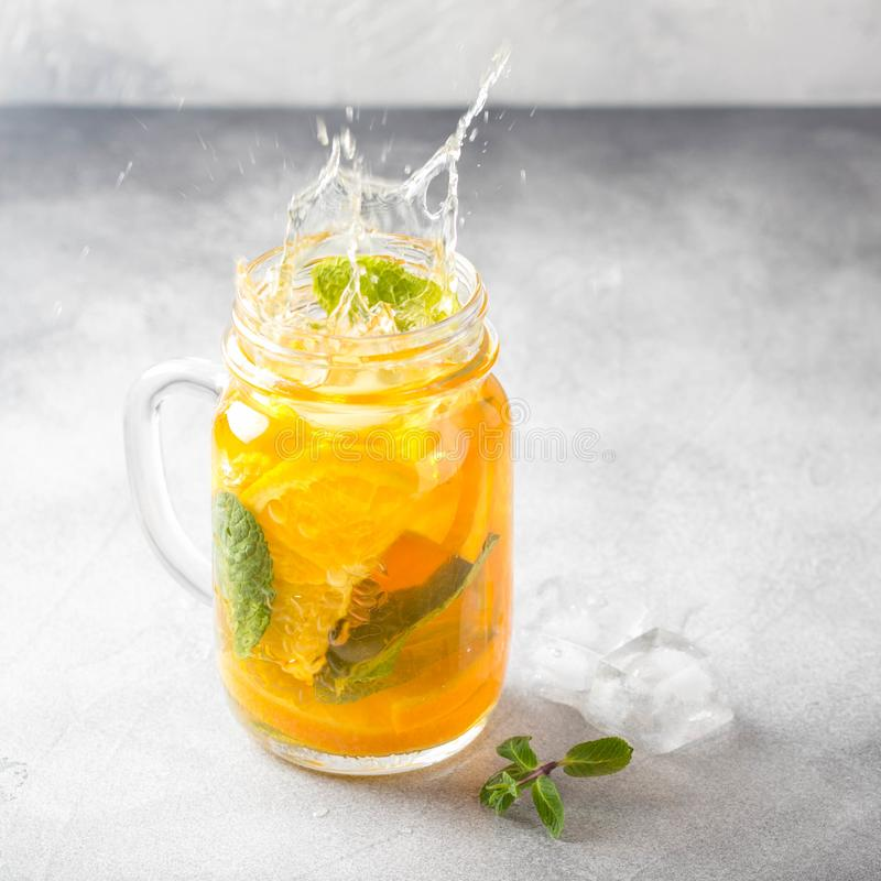 Cold tea with orange, mint and ice, sweet summer drink, refreshing lemonade, juicy cocktail. Spray, splash. Cold tea with orange, mint and ice, sweet summer stock photography