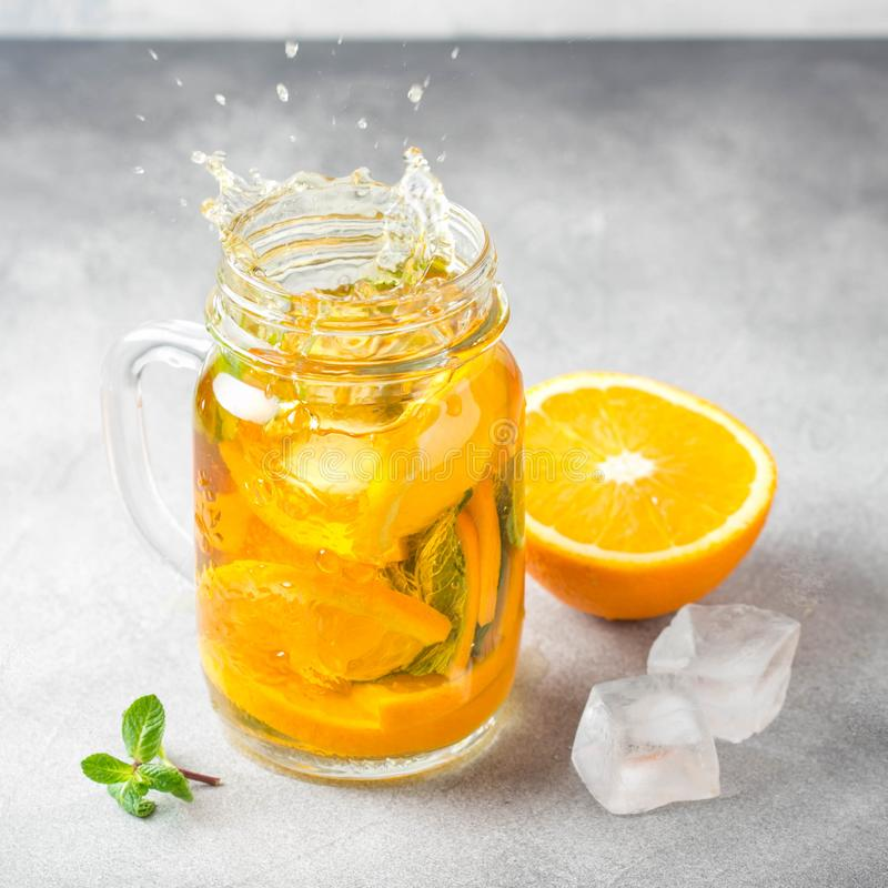 Cold tea with orange, mint and ice, sweet drink, refreshing lemonade, juicy cocktail. Spray, splash. Cold tea with orange, mint and ice, sweet summer drink royalty free stock photography