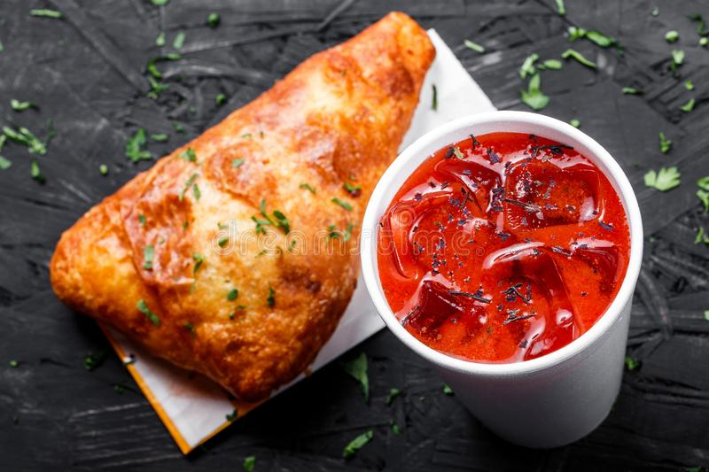 Cold tomato gazpacho soup in glass for summer with ice and Georgian khachapuri - flatbread with cheese on dark wooden background stock images