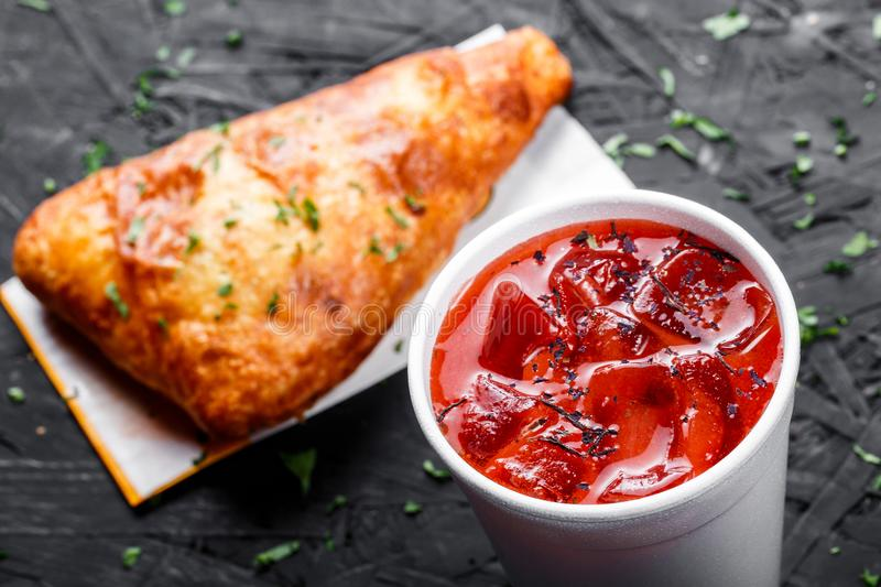 Cold tomato gazpacho soup in glass for summer with ice and Georgian khachapuri - flatbread with cheese on dark wooden background stock photos