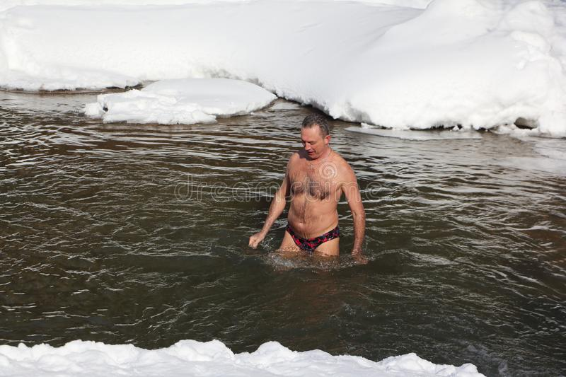 Cold trainings, man swimming in the Belokurikha River. Taken on - March, 11, 2017 in Altai Territory, Belkurikha city, Russia. Altai Territory, Belkurikha city stock photography