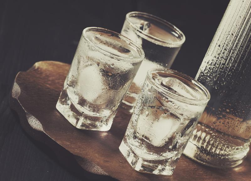 Cold vodka in shot glass and bottle, the concept of alcohol dependence, selective focus royalty free stock images