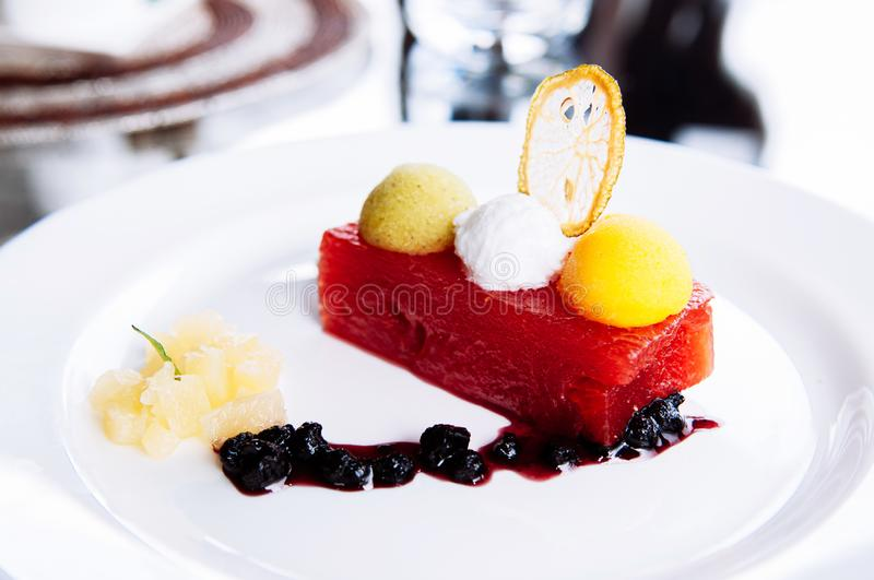 Cold watermelon and fruits ice cream sorbet and berries sauce in white plate royalty free stock image