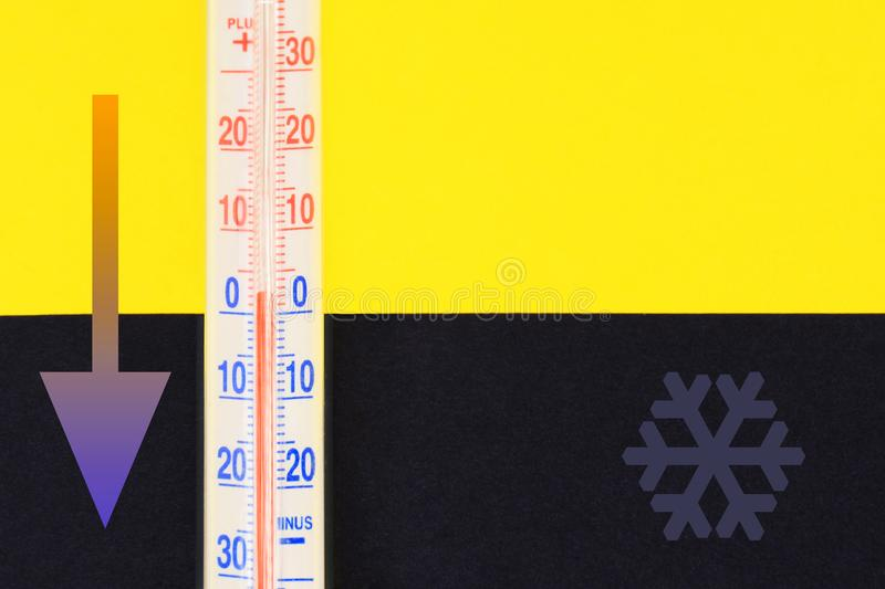 Cold weather concept. Thermometer closeup. On yellow and dark background stock photography