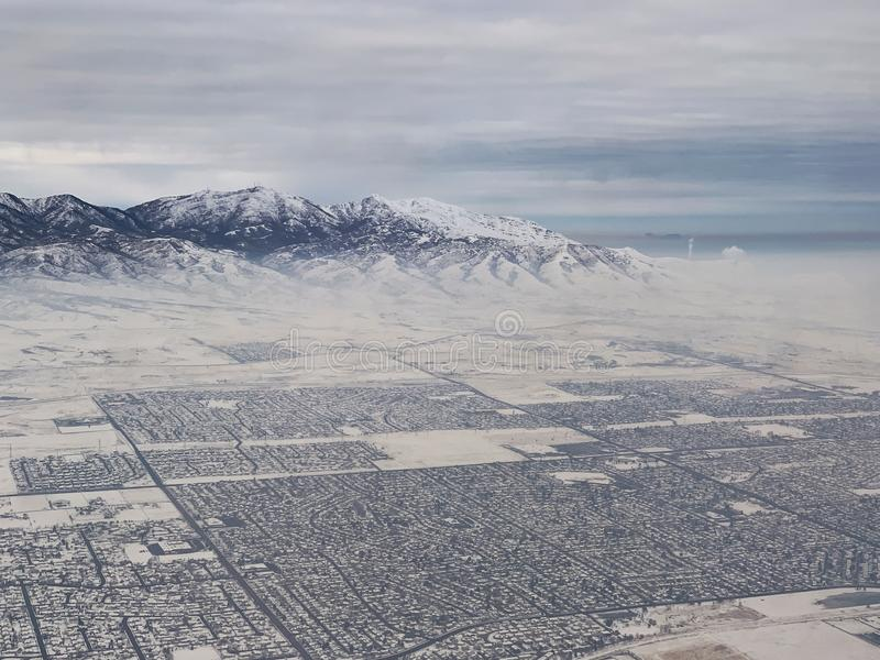 Snow covered mountains overlooking Slat Lake City in winter. Cold, white, winter landscape with mountains and Salt Lake City royalty free stock photography