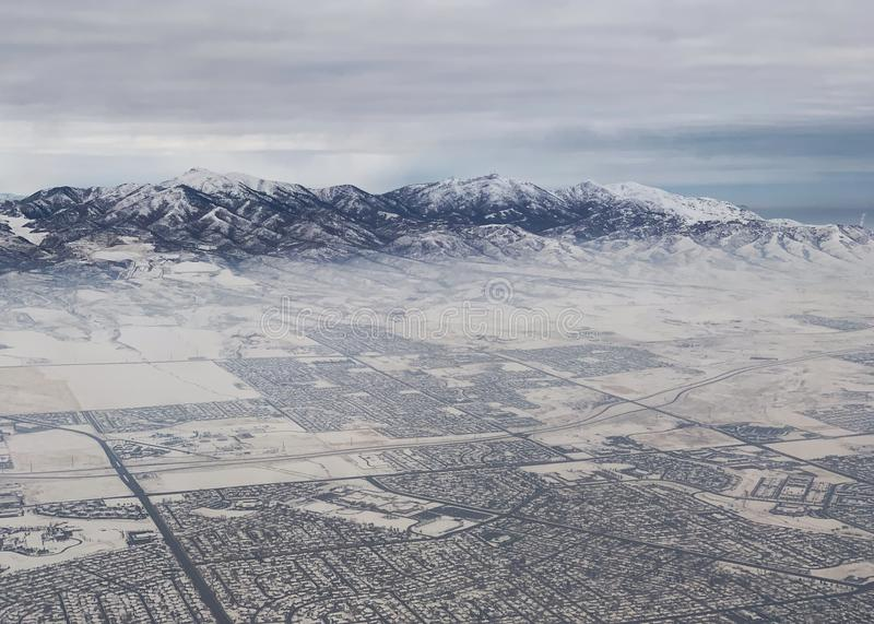 Snow covered mountains overlooking Slat Lake City in winter. Cold, white, winter landscape with mountains and Salt Lake City royalty free stock image