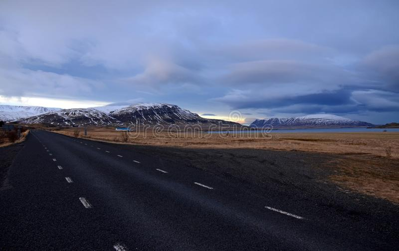 Cold winter morning on the road No. 1 in Iceland amid Mountains in snow caps and blue sky. In dark clouds royalty free stock photography