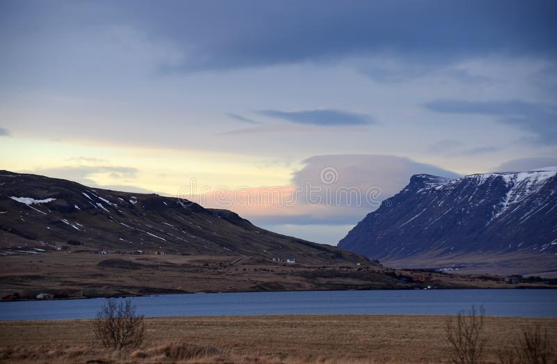 Cold winter morning on the road No. 1 in Iceland amid Mountains in snow caps and blue sky. In dark clouds stock photos