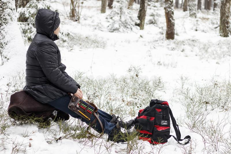 It is cold in winter, it is snowing. Girl with a compass map and odometer in hand, paves the route. there is toning.  stock photography