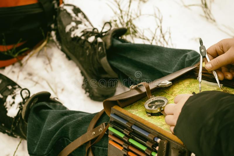 It is cold in winter, it is snowing. Girl with a compass map and odometer in hand, paves the route. there is toning.  royalty free stock photo
