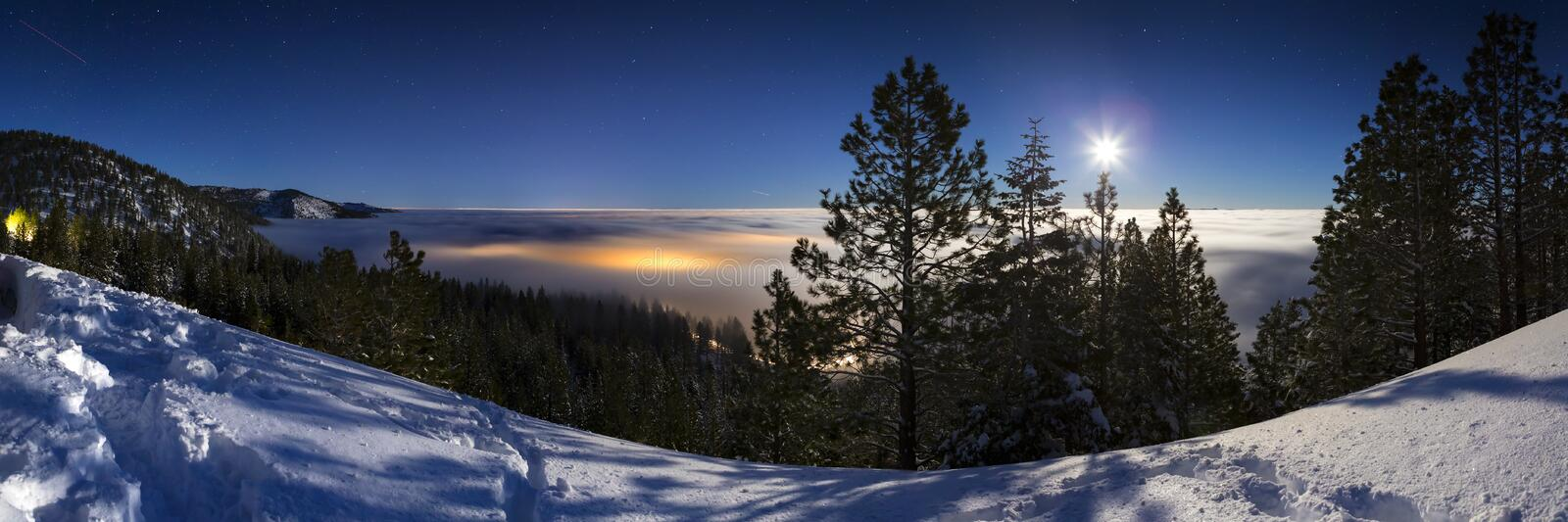 Cold Winter Snowy landscape at night with cloud inversion covering city lights that glow underneath the cloud cover. Lit with moo. Nlight and the sky has stars stock photo