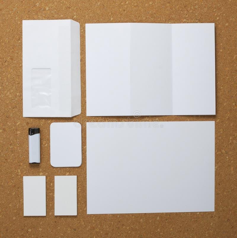 Coleção branca dos artigos de papelaria no fundo do corkboard. foto de stock royalty free