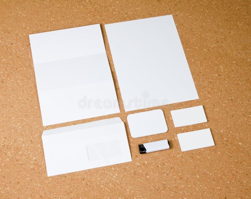 Coleção branca dos artigos de papelaria no fundo do corkboard imagem de stock