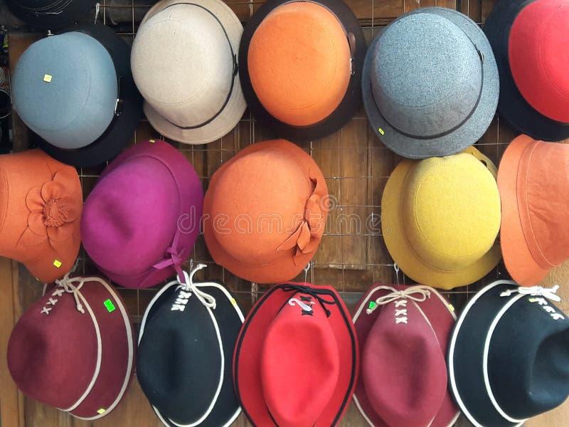 Coleção colorida do arco-íris dos chapéus na exposição da loja nas laranjas, nos azuis, nos vermelhos, nos amarelos e nos roxos imagem de stock royalty free