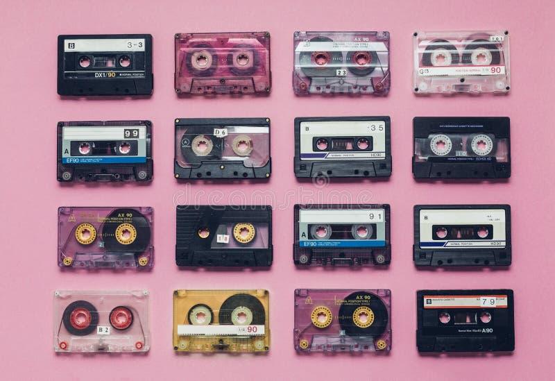 Coleção de cassetes áudio retros na fileira no fundo lilás Conceito retro da música da tecnologia fotografia de stock