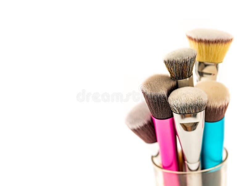 Coleção de escovas cosméticas da fundação no recipiente de vidro do frasco com fundo branco fotografia de stock