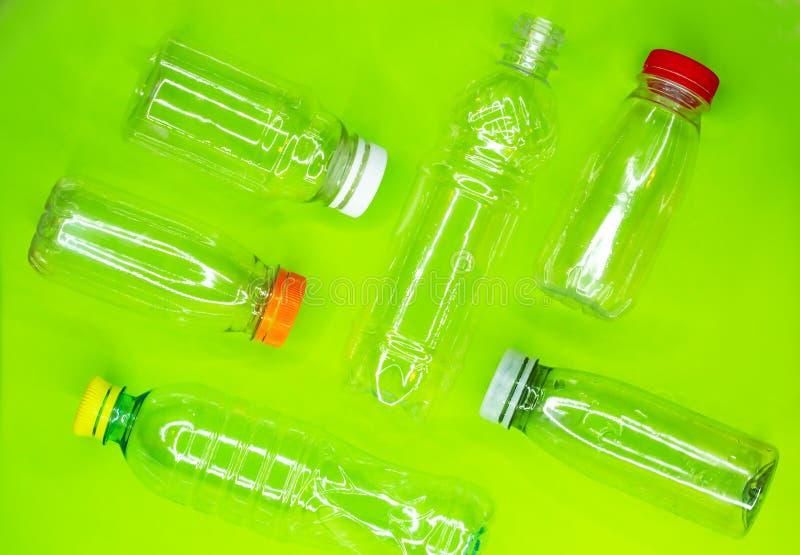 Coleção de garrafas plásticas usadas vazias no fundo verde Reciclando o conceito do desperdício Vista superior foto de stock royalty free