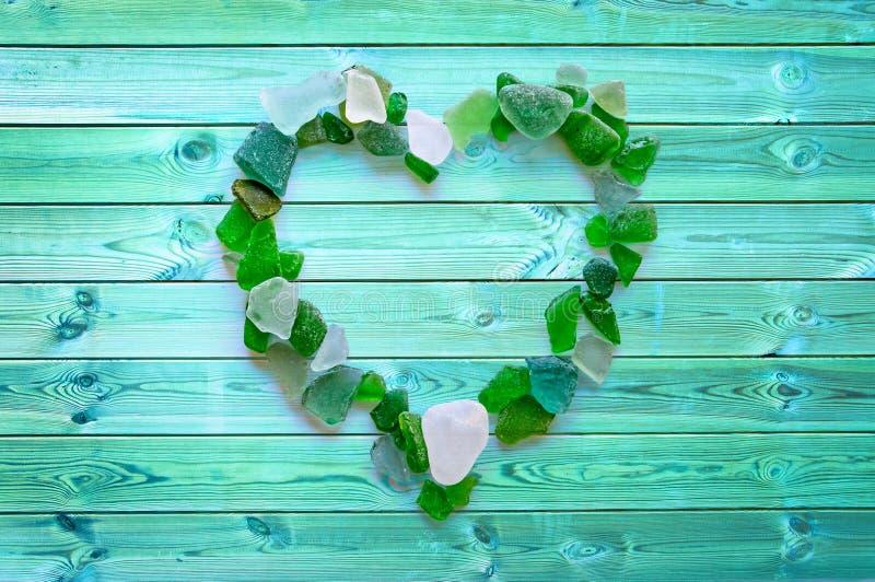 Coleção de vidro da praia na forma de um coração em pranchas azuis fotos de stock royalty free