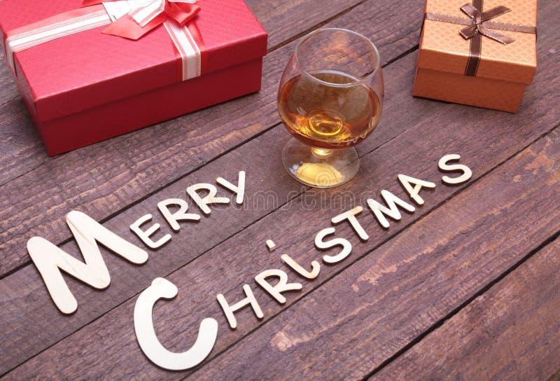 Coleção do Natal, caixa de presentes, conhaque de vidro e bola decorativa, no fundo de madeira imagem de stock royalty free