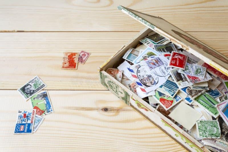 Cole??o dos selos postais de pa?ses diferentes na caixa velha que encontra-se em uma tabela de madeira foto de stock royalty free