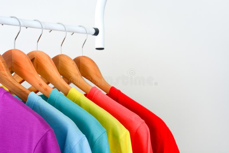 Coleção dos t-shirt coloridos do arco-íris que penduram no gancho de roupa de madeira na cremalheira da roupa sobre o fundo branc fotografia de stock