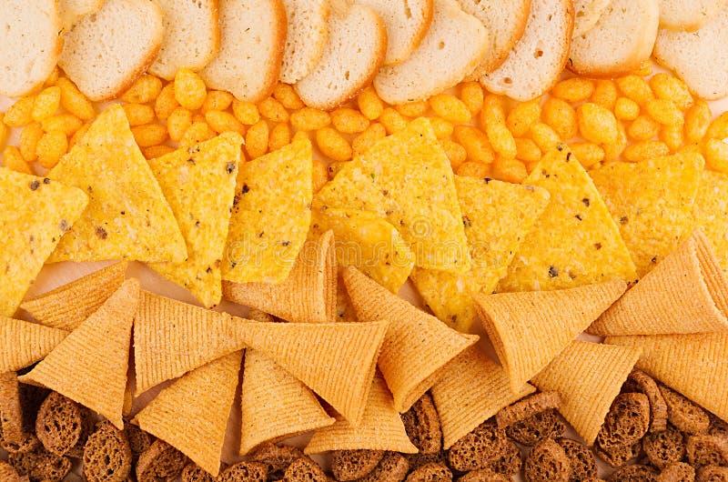 Coleção picante brilhante dos petiscos - os nachos, brindes corado, pão torrado do centeio, milho colam como o fundo da xadrez Vi fotografia de stock