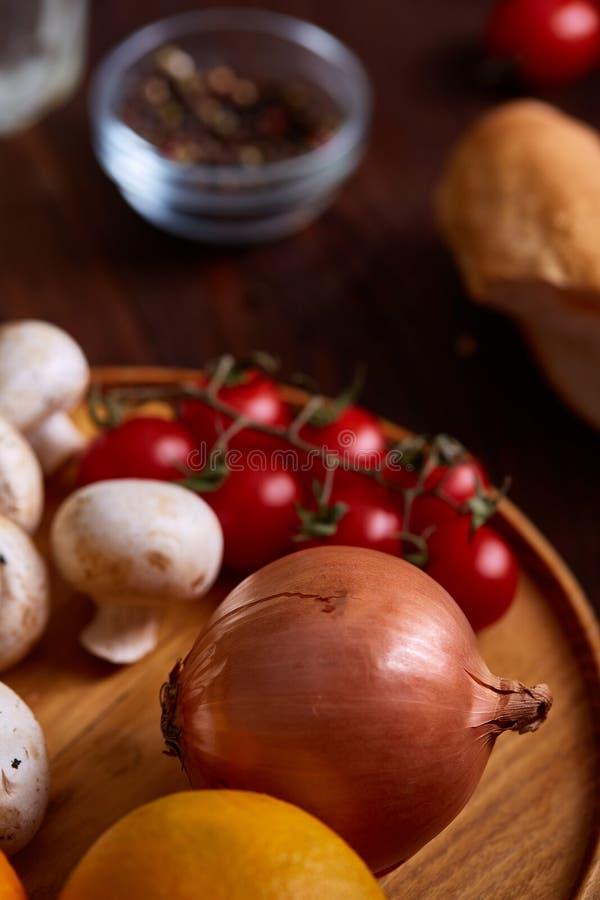 Coleção vegetal da vitamina com tomates cereja, cogumelos e cebolas vermelhas em um fundo de madeira foto de stock royalty free