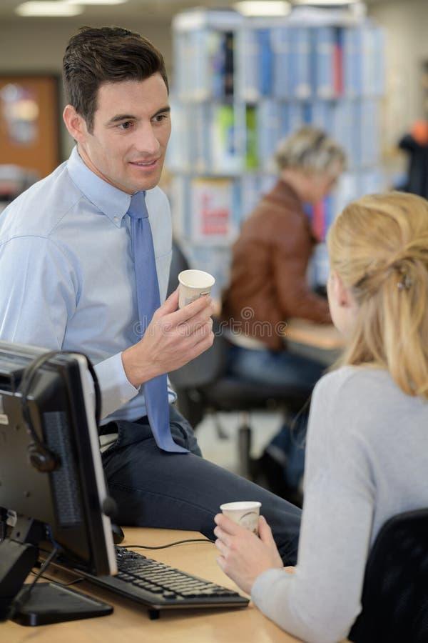 Coleagues che ha pausa caffè all'ufficio fotografia stock libera da diritti