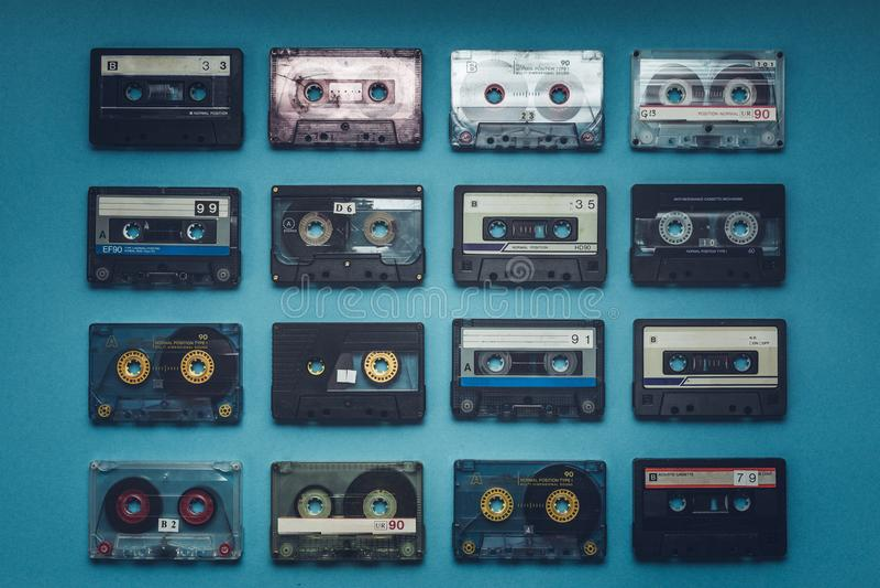 Colección de cintas de audio retras en el fondo azul, visión superior Concepto retro de la música de la tecnología imagen de archivo