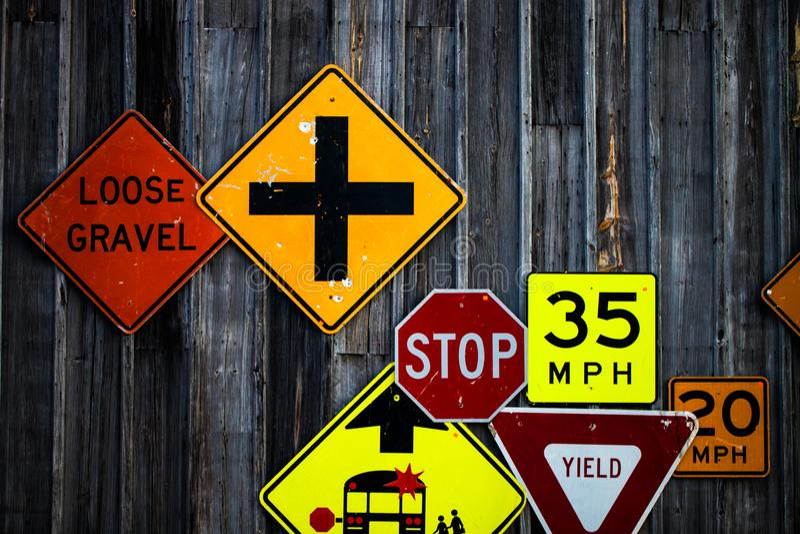 Colección de diversas señales de tráfico en la pared de madera rústica imagen de archivo libre de regalías