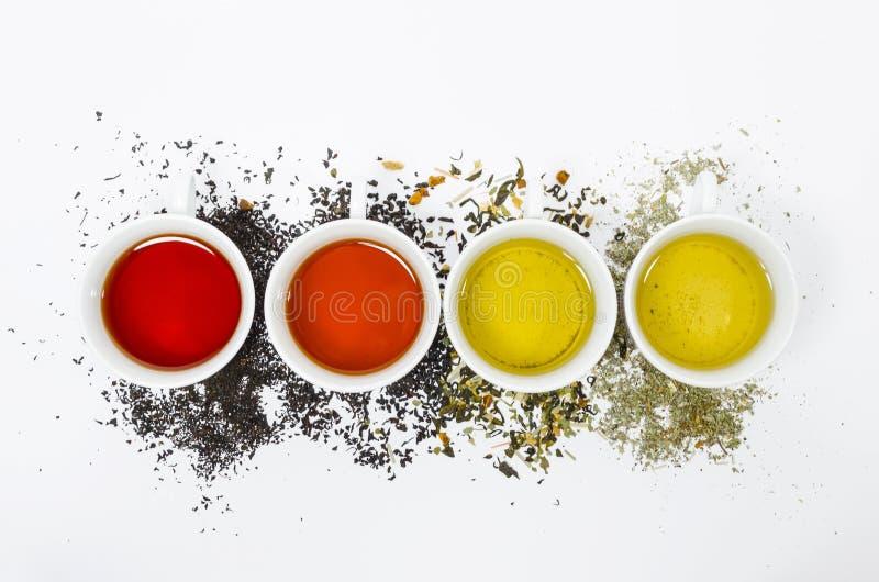 Colección de diversos tés en tazas con las hojas de té en un fondo blanco imagenes de archivo