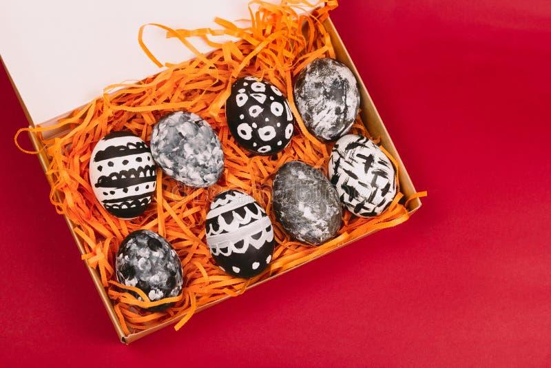 colección de huevos de Pascua blancos y negros teñidos en caja en un fondo rojo fotografía de archivo libre de regalías