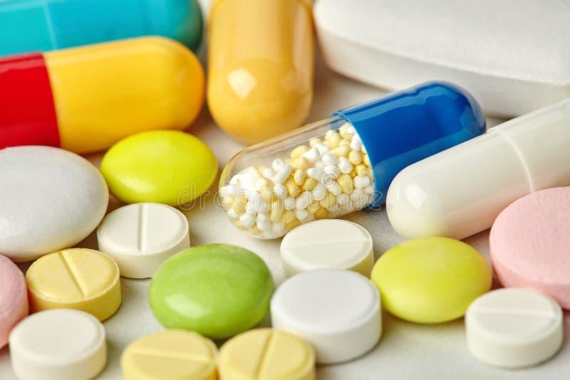 Colección de la farmacia de las píldoras en el fondo de papel Diversas clases coloridas del tamaño drogan la visión macra antibió imagen de archivo