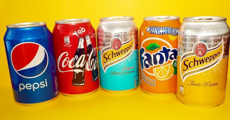 Colección de las latas de soda aislada en fondo amarillo fotos de archivo libres de regalías