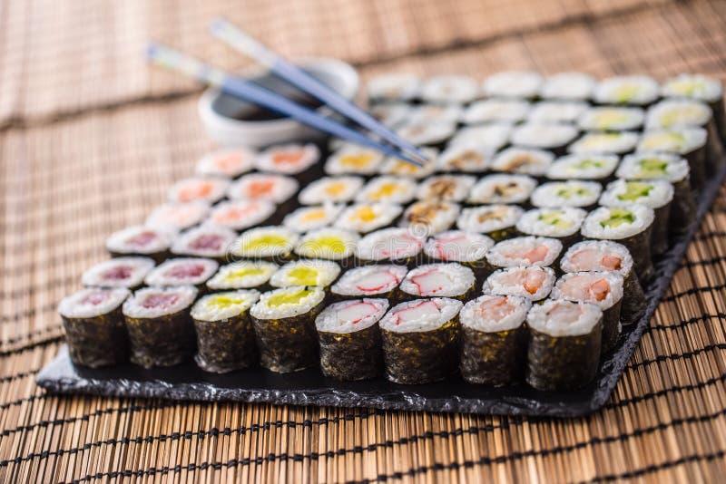 Colección de maki del sushi en tablero de la pizarra con la salsa y las tajadas de soja imagen de archivo
